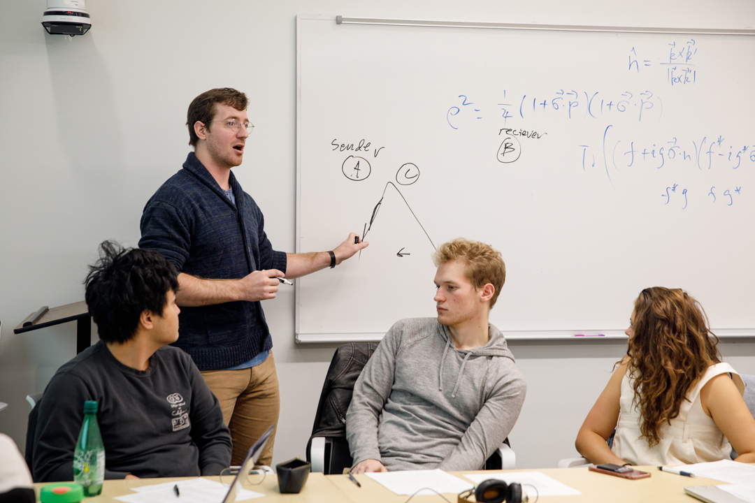 A Physics teaching assistant pointing at the white board while 3 undergraduate students listen in