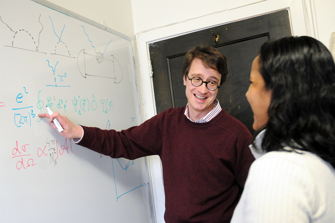 Professor of Physics Harald Griesshammer (left) point at a white board while talking to a female student (right)