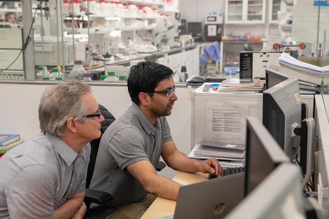 TA Raju Timsina talks with Mark Reeves in the SEH biophysics lab, surrounded by laboratory equipment and computers