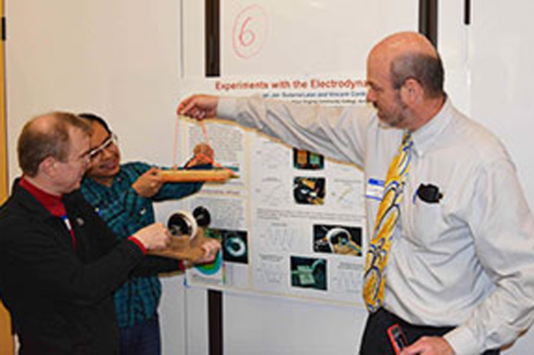 Faculty and students look at physics exhibits.