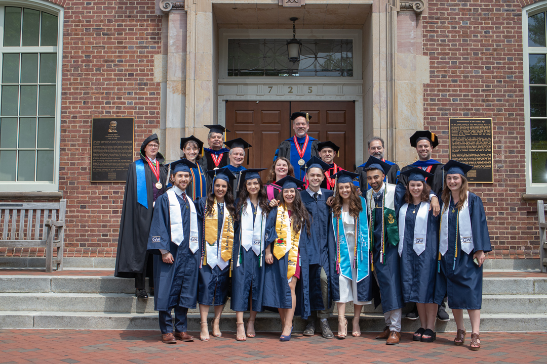 A group of students in their graduation caps and gowns standing with professors in their academic regalia outside of Corcoran Hall.