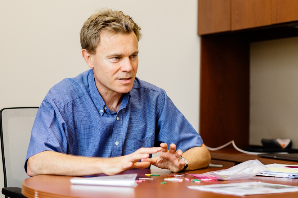 Neil Johnson sitting at a desk with papers in front of him