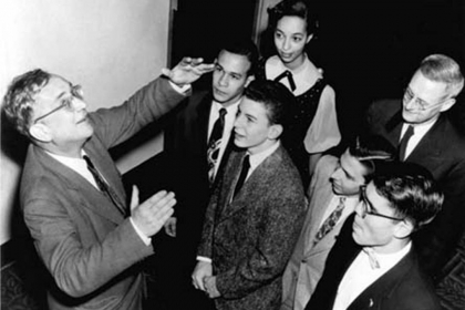 George Gamow in a black-and-white photograph speaking to a group of male students
